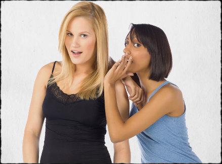 girl whispering in another girls ear